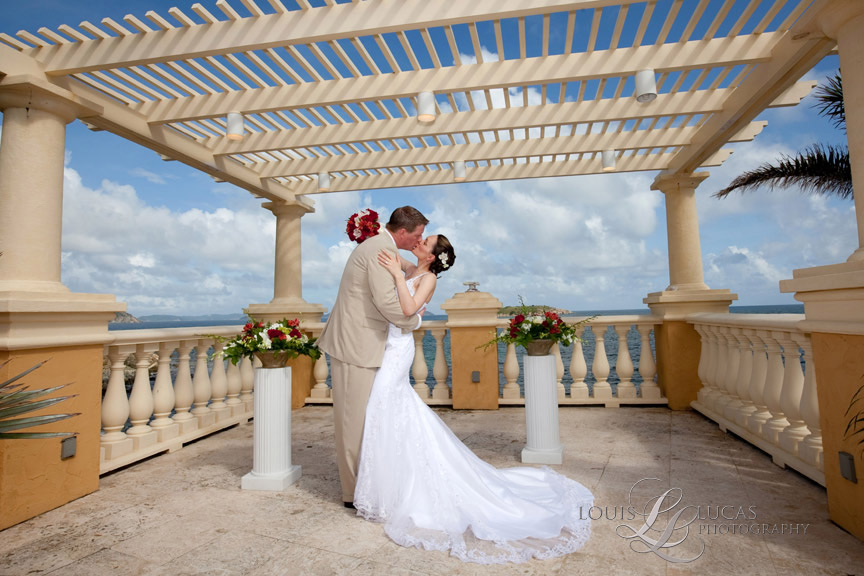 Bride and groom kiss under the caribbean sky